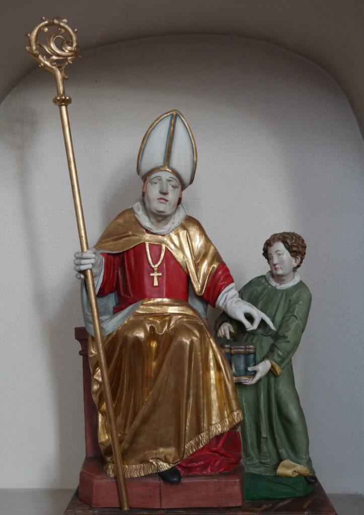 Hl. Remigius. Remigius mit dem Bischofsstab in der Hand, flankiert von einem Diakon, der ihm ein Ölgefäß reicht
